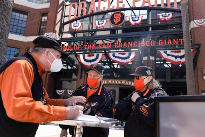 SAN FRANCISCO, CALIFORNIA - APRIL 09: San Francisco Giants fans Dave Harding of San Leandro, center, and his wife, Nancy Faltisek, check in at one of the vaccination/negative test verification booths to show the proof of their COVID-19 vaccinations before being admitted to Oracle Park at the Giants' season home opener on Friday, April 9, 2021, in San Francisco, Calif. (Dai Sugano/Bay Area News Group)