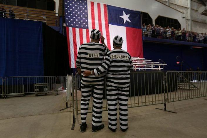 Trump supporters costumed as Bill and Hillary Clinton in prison uniforms sing the national anthem before a rally for Donald Trump in Austin, Texas, on Tuesday. (Carlo Allegri/Reuters)