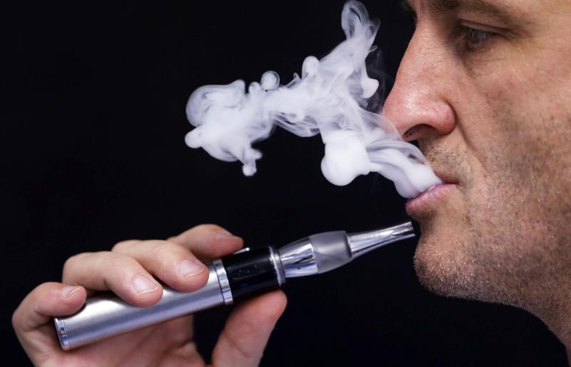 """Charly Pairaud, deputy director of VDLV (""""Vincent dans les Vapes"""") e-liquids maker, demonstrates the use of an electronic cigarette in his factory in Pessac, in this file photo taken October 9, 2013. The Oxford English Dictionary named vape - the word used for drawing on an electronic cigarette instead of a burning stick of tobacco - as its 2014 word of the year.   REUTERS/Regis Duvignau/Files  (FRANCE - Tags: BUSINESS HEALTH SOCIETY)"""