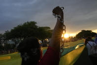 A demonstrator raises a chain during a protest against President Jair Bolsonaro calling for his impeachment over his government's handling of the pandemic and accusations of corruption in the purchases of COVID-19 vaccines, in in Brasilia, Brazil, Saturday, Oct. 2, 2021. (AP Photo/Eraldo Peres)
