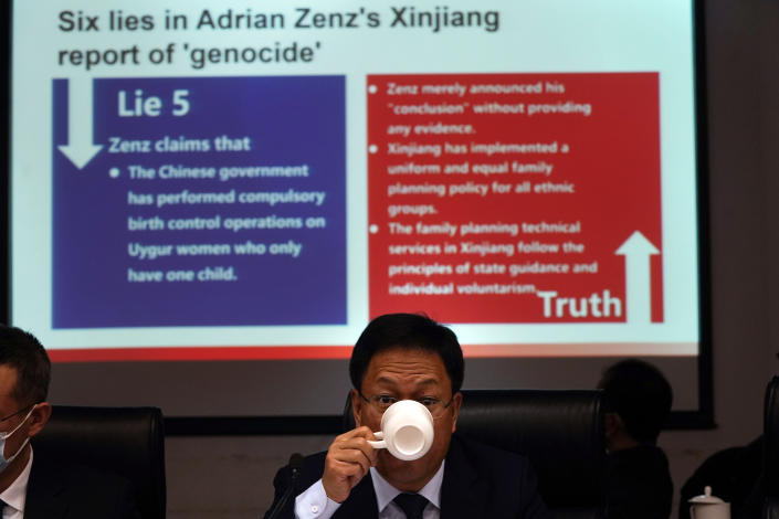 """Xu Guixiang, a deputy spokesperson for the Xinjiang regional government, drinks from a cup near a slide refuting claims of genocide during a press conference in Beijing, China. The Chinese official on Monday denied Beijing has imposed coercive birth control measures among Muslim minority women, following an outcry over a tweet by the Chinese Embassy in Washington claiming that government polices had freed women of the Uighur ethnic group from being """"baby-making machines."""" (AP Photo/Ng Han Guan)"""