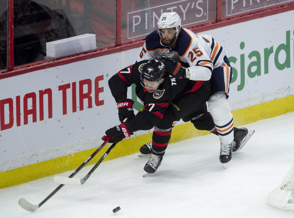 Edmonton Oilers defenseman Darnell Nurse pressures Ottawa Senators left wing Brady Tkachuk as he attempts to pass the puck to the front of the net during the second period of an NHL hockey game Wednesday, April 7, 2021, in Ottawa, Ontario. (Adrian Wyld/The Canadian Press via AP)