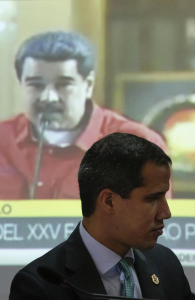 Venezuela's opposition leader and self-proclaimed interim President of Venezuela, Juan Guaidó, shows a video of Venezuelan President Nicolas Maduro, during a meeting with lawmakers at the administrative headquarters of the National Assembly in Caracas, Venezuela, Tuesday, Sept. 3, 2019. Guaidó announced he will allow the use of satellite technology to facilitate the location and detection of irregular Colombian groups that might be in Venezuela, adding he has already started cooperating with Colombia's government to locate them. (AP Photo/Andrea Hernandez Briceño)