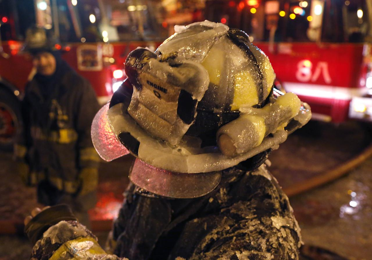 A Chicago firefighter's helmet is covered with ice from single digit temperatures during a five-alarm blaze in a warehouse on the city's South Side, Bridgeport neighborhood Wednesday, Jan. 23, 2013, in Chicago. (AP Photo/Charles Rex Arbogast)