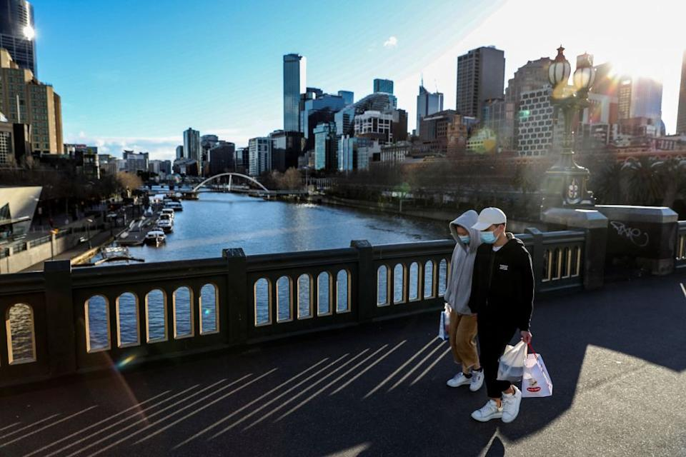 Face mask-clad pedestrians walking through Southbank in Melbourne following a fresh lockdown amid a resurgence in coronavirus cases.
