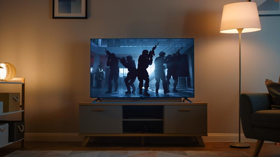 Shot of a TV with an Action Movie with Soldiers. It's Evening and Room at Home Has Working Lamps.