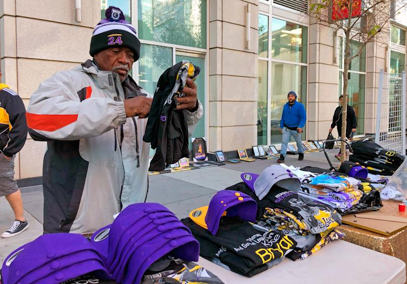 Donnell Dorsey arranges Kobe Bryant memorabilia outside the Staples Center in Los Angeles, Monday, Feb. 24, 2020. Dorsey slept along Figueroa Street Sunday night to claim a spot to sell merchandise outside the public memorial for Kobe Bryant and his daughter, Gianna. Dorsey said he sold out of Bryant-related T-shirts and hats five times the day after the basketball superstar died.