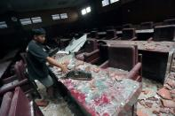 A man cleans up a damaged courtroom affected by an earthquake of magnitude 5.9 struck in the ocean 91 km (57 miles) south-southeast of Blitar