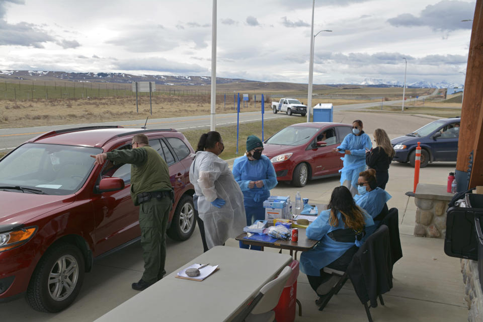 In this Thursday, April 29, 2021, photo, a U.S. Border Patrol agent directs a driver after the passenger received a COVID-19 vaccine from nurses of the Blackfeet tribe at the Piegan-Carway border crossing near Babb, Mont. The Blackfeet tribe in northern Montana gave out surplus vaccines in April to its First Nations relatives and others from across the border. (AP Photo/Iris Samuels)