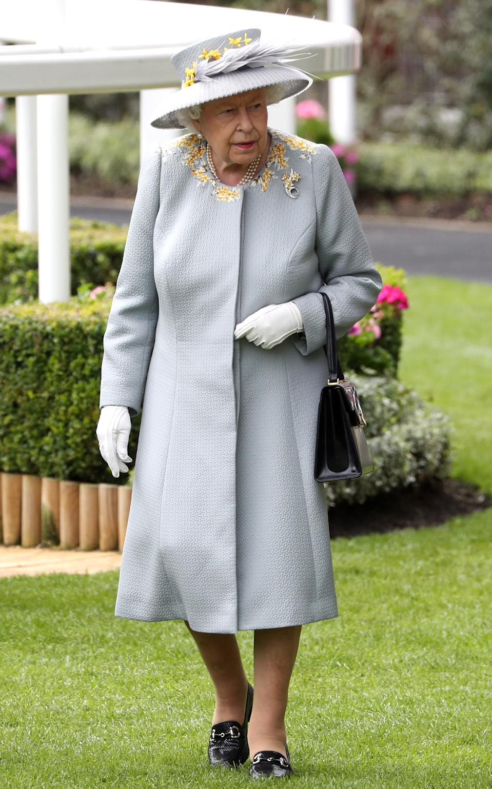 The Queen wore a metal grey coat and hat with yellow accents. <em>[Photo: PA]</em>