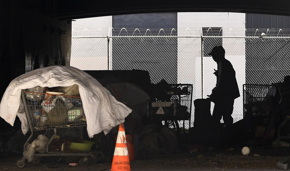 """FILE - In this May 21, 2020 file photo, a man is seen at a homeless encampment that sits under Interstate 110 near Ramirez Street during the coronavirus outbreak in downtown Los Angeles. A coalition in California is proposing legislation to boost taxes on wealthy multi-national corporations to raise more than $2 billion a year to end homelessness. Supporters say Assembly Bill 71, if approved, would """"reinvent"""" the state's approach to solving homelessness. (AP Photo/Mark J. Terrill, File)"""