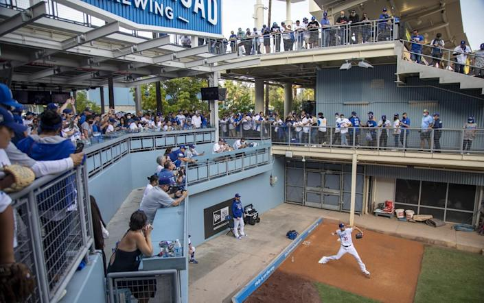 Fans get a glimpse of Los Angeles Dodgers starting pitcher Max Scherzer warming up in the bullpen