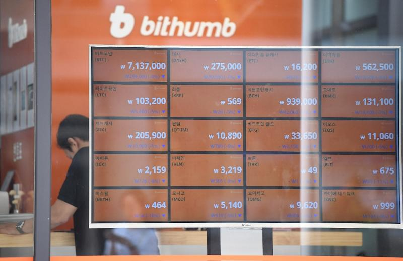 A man stands behind a screen showing exchange rates of cryptocurrencies at Bithumb virtual currency exchange in Seoul on June 20, 2018; Facebook's new Libra digital money is being backed by cash in an effort to maintain a stable value (AFP Photo/Jung Yeon-je)