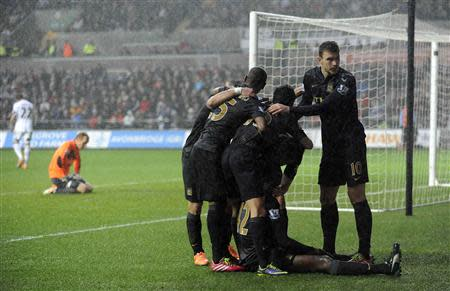 Manchester City's Yaya Toure (on ground) celebrates with his teammates after scoring a goal against Swansea City during their English Premier League soccer match at the Liberty Stadium in Swansea, Wales, January 1, 2014. REUTERS/Rebecca Naden