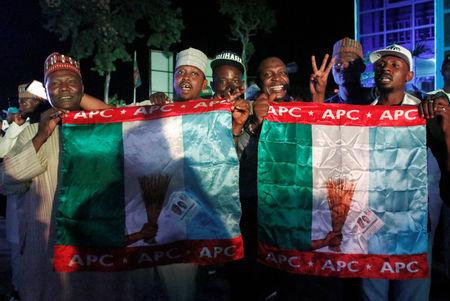 Supporters of Nigeria's President Muhammadu Buhari carry APC flags as they celebrate at the campaign headquarters of All Progressives Congress (APC) in Abuja, Nigeria February 26, 2019. REUTERS/Nneka Chile