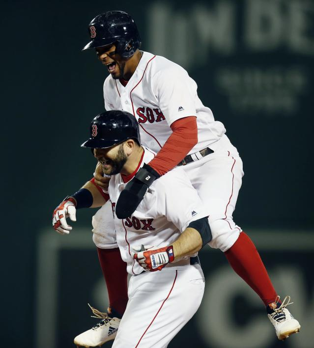 Boston Red Sox's Mitch Moreland, bottom, celebrates his game-winning RBI single with Xander Bogaerts during the ninth inning of a baseball game against the Houston Astros in Boston, Sunday, Sept. 9, 2018. (AP Photo/Michael Dwyer)