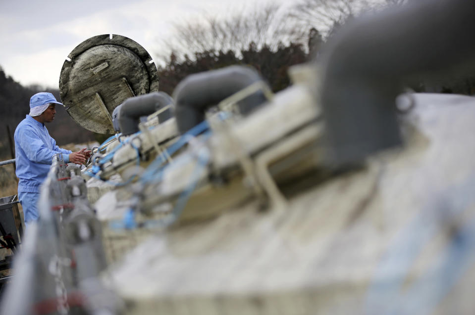FILE - In this March 6, 2015, file photo, a worker of Yagisawa Shoten Co., checks soy sauce tanks of the company's new factory in Ichinoseki, Iwate Prefecture, northeastern Japan. Just a month after a tsunami as high as 17 meters (55 feet) smashed into the city of Rikuzentakata, soy sauce maker Michihiro Kono inherited his family's two-century-old business from his father. Later this year the ninth generation owner of Yagisawa Shoten Co. will open a new factory on the same ground where his family started making soy sauce in 1807. (AP Photo/Eugene Hoshiko)