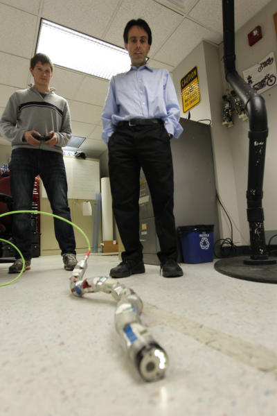 In this April 18, 2012, photo, Carnegie Mellon University professor Howie Choset, right, stands behind a robot as staff researcher Florinan Enner uses a controller to demonstrate how it moves at their lab on campus in Pittsburgh. Scientists and doctors are using the creeping metallic tools to perform surgery on hearts, prostate cancer and other diseased organs. (AP Photo/Keith Srakocic)