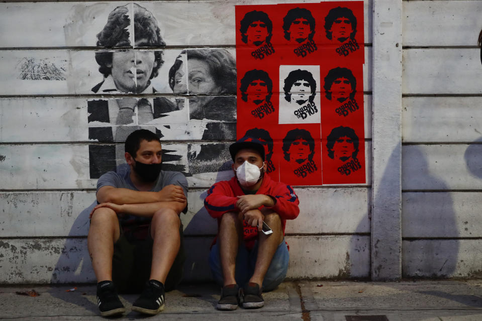 Soccer fans sit in front of posters of Diego Maradona, outside the Argentinos Juniors stadium, where he started as a professional footballer in Buenos Aires, Argentina, Wednesday, Nov. 25, 2020. The Argentine soccer great who was among the best players ever and who led his country to the 1986 World Cup title before later struggling with cocaine use and obesity, died from a heart attack on Wednesday at his home in Buenos Aires. He was 60. (AP Photo/Marcos Brindicci)