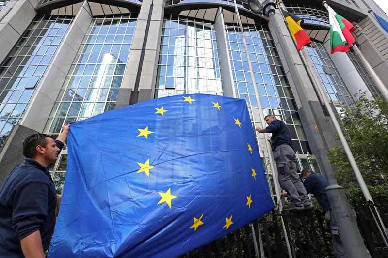 Workers adjust a European flag outside the EU Parliament ahead of the EU elections in Brussels