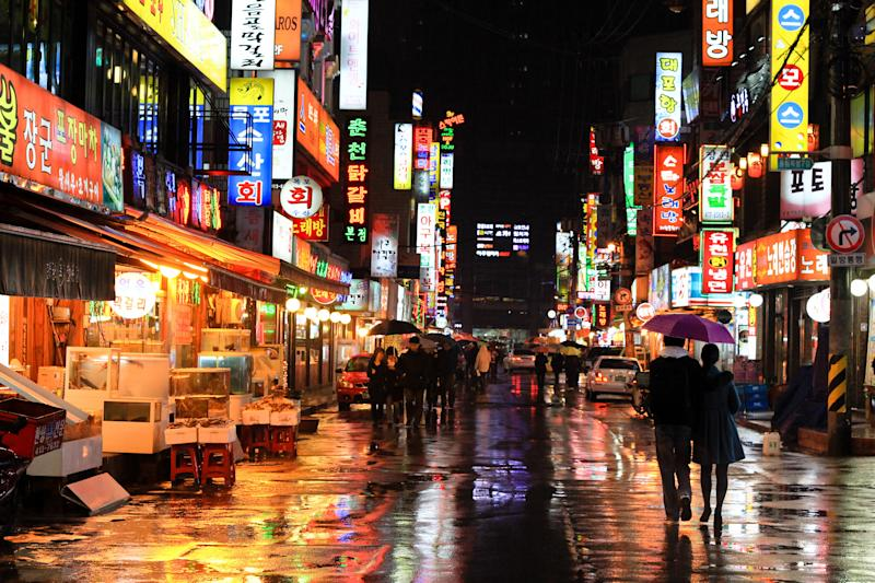 Colorful neon reflections of wet Seoul street taken at night at rain in Korea, Asia.
