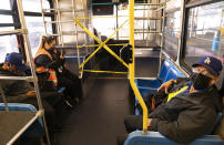 Airport workers take a shuttle bus between terminals at Los Angeles International Airport in Los Angeles, Wednesday, Nov. 25, 2020. Residents were urged to avoid nonessential travel during what is typically the busiest travel period of the year. Anyone entering California was advised to quarantine for two weeks. (AP Photo/Damian Dovarganes)