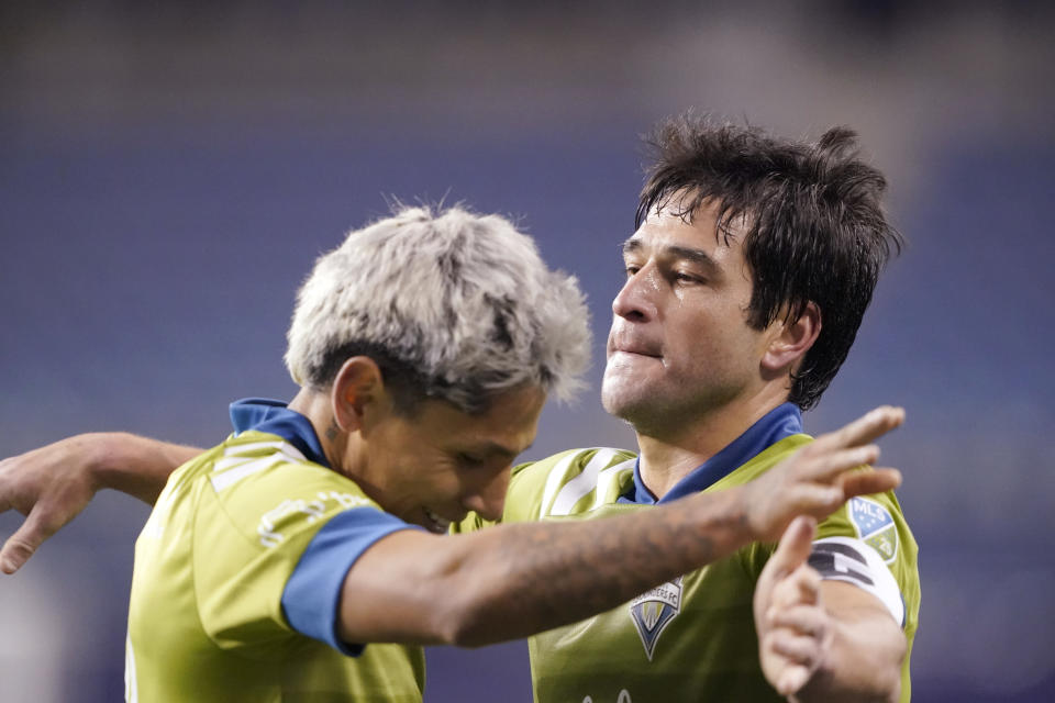 Seattle Sounders' Raul Ruidiaz, left, and Nicolas Lodeiro embrace after the team's 1-0 win over FC Dallas in an MLS playoff soccer match Tuesday, Dec. 1, 2020, in Seattle. (AP Photo/Ted S. Warren)