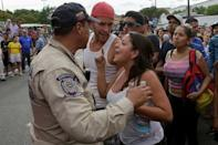 A woman argues with a riot police officer during a protest over food shortage and against Venezuela's government in Caracas, Venezuela June 14, 2016. REUTERS/Marco Bello