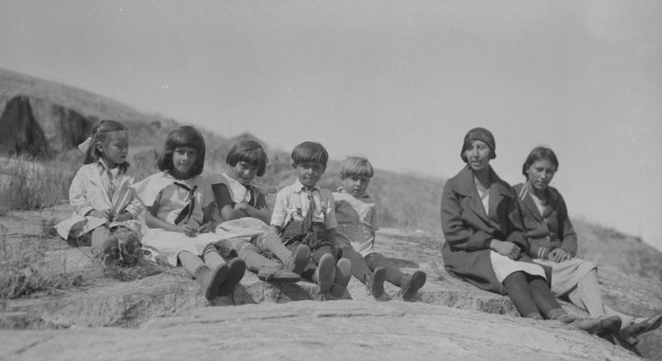 """<span class=""""caption"""">Queen's University professor Celeste Pedri-Spade says a basic first question to determine identity is: 'Who is your grandmother?"""" Here a group of Métis children and two women sitting on a large rock, Fort Chipewyan, Alberta, 1931</span> <span class=""""attribution""""><span class=""""source"""">H. S. Spence, Canada. Department of Mines and Technical Surveys. Library and Archives Canada, PA-014406 /</span>, <a class=""""link rapid-noclick-resp"""" href=""""http://creativecommons.org/licenses/by-nc/4.0/"""" rel=""""nofollow noopener"""" target=""""_blank"""" data-ylk=""""slk:CC BY-NC"""">CC BY-NC</a></span>"""