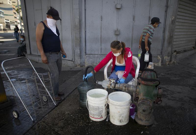 People wearing protective masks as a precaution against the spread of the new coronavirus collect water from a hydrant, in Caracas, Venezuela, Tuesday, March 17, 2020. President Nicolas Maduro ordered citizens to stay home, and to wear a mask when in public. The vast majority of people recover from the new virus. (AP Photo/Ariana Cubillos)