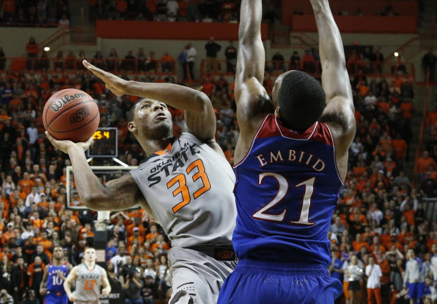 Oklahoma State guard Marcus Smart (33) shoots in front of Kansas center Joel Embiid (21) in the second half of an NCAA college basketball game in Stillwater, Okla., Saturday, March 1, 2014. Oklahoma State won 72-65. (AP Photo/Sue Ogrocki)