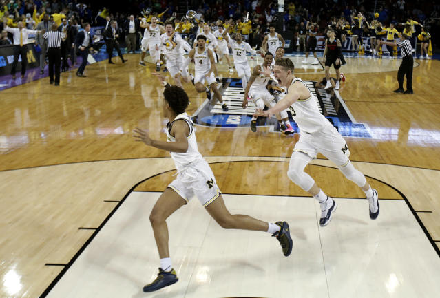 Michigan guard Jordan Poole (2) is chased by teammates after making a 3-point basket at the buzzer to win an NCAA men's college basketball tournament second-round game against Houston on Saturday, March 17, 2018, in Wichita, Kan. Michigan won 64-63. (AP Photo/Charlie Riedel)