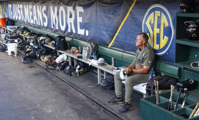 Vanderbilt coach Tim Corbin sits in the dugout watching his team celebrate their win over Mississippi after a Southeastern Conference tournament NCAA college baseball championship game, Sunday, May 26, 2019, in Hoover, Ala. (AP Photo/Butch Dill)