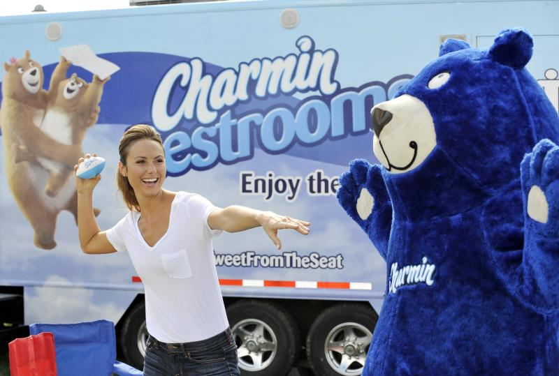 Woman throwing small football in front of a blue bear mascot, with semitrailer in background displaying a Charmin ad