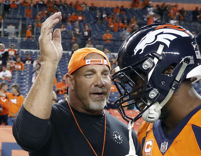 "FILE - In this Sept. 11, 2017, file photo, professional wrestler Bill Goldberg, left, greets Denver Broncos outside linebacker Von Miller prior to an NFL football game against the Los Angeles Chargers, Monday, Sept. 11, 2017, in Denver. Bill Goldberg found his toughest tag-team partner yet. ""The Goldbergs."" Goldberg is set to star in Wednesday's, March 21, 2018, episode. But the wrestling great has a bigger date ahead when he's inducted into the WWE Hall of Fame on WrestleMania weekend. (AP Photo/Jack Dempsey, File)"