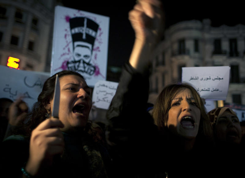 """An Egyptian woman activist holds a knife while taking part in a protest for women against sexual harassment and against the Islamist dominated Shura Council for blaming women for the attacks against them, in Cairo, Egypt, Tuesday, Feb. 12, 2013. Arabic in the background reads """"Shura Council gives the harassment excuses."""" (AP Photo/Nasser Nasser)"""