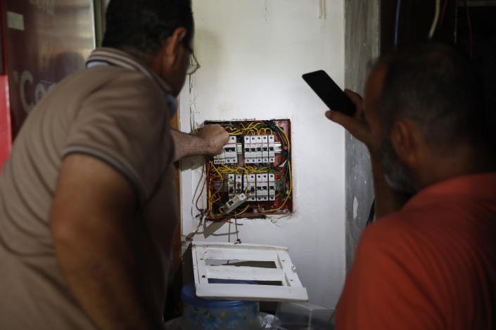 A Lebanese man, right, lights by his mobile phone for an electrician worker, left, who sets an electricity switch for a coffeeshop from a private-owned generators that provide power to homes and businesses, after the power remains shut off about 20 hours a day in Beirut, Lebanon, Wednesday, July 29, 2020. The multiple crises may seem like a standard summer in Lebanon, a country constantly vaulting from one disaster to the other. Only this time they come on top of financial ruin, collapsing institutions, hyperinflation and rapidly rising levels of poverty and unemployment. (AP Photo/Hussein Malla)