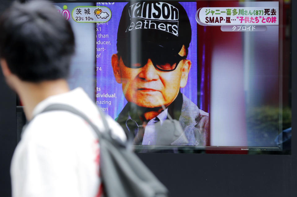 A passer-by watches a TV news reporting Johnny Kitagawa's passing away in Tokyo Wednesday, July 10, 2019. Kitagawa, who produced famous boybands including Arashi and SMAP and was a kingpin of Japan's entertainment industry for more than half a century, has died Tuesday from a subarachnoid hemorrhage at a Tokyo hospital. He was 87. (Kyodo News via AP)