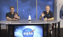 In this frame grab from NASA TV video, astronauts Bob Behnken, left, and Doug Hurley wave during a news conference, Tuesday, Aug. 4, 2020, in Houston. The two NASA astronauts returned to Earth on Sunday in a dramatic, retro-style splashdown carried out by Elon Musk's SpaceX company. (NASA TV via AP)