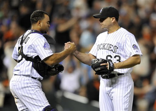 Colorado Rockies catcher Wilin Rosario (20) celebrates with relief pitcher Rafael Betancourt (63) following a baseball game against the San Francisco Giants on Friday, May 17, 2013, in Denver. Colorado Defeated San Francisco 10-9. (AP Photo/Jack Dempsey)