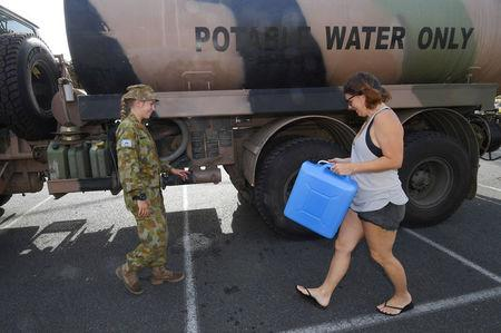 A local arrives to collect drinking water from an Australian Army tanker after Cyclone Debbie caused damage to local drinking water supplies in the town of Airlie Beach, located south of the northern Queensland town of Townsville in Australia, March 31, 2017.      AAP/Dan Peled/via REUTERS