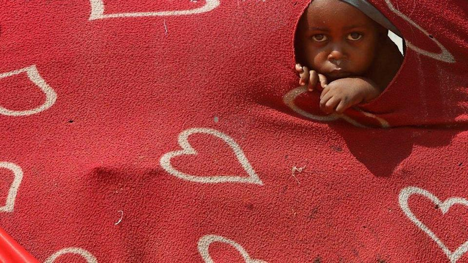 A child looks at the camera through a hole in a blanket which is attached to a temporary shelter.