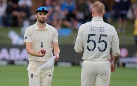 Mark Wood Bowler of England, left, gives the ball to teammate Ben Stokes to dry during day two of the third cricket test between South Africa and England in Port Elizabeth, South Africa, Saturday, Jan. 18, 2020. - Credit: AP