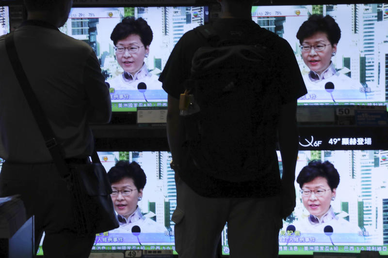 Residents watch a broadcast of Chief Executive Carrie Lam speaking at a press conference held in Hong Kong on Saturday, June 15, 2019. Lam said she will suspend a proposed extradition bill indefinitely in response to widespread public unhappiness over the measure, which would enable authorities to send some suspects to stand trial in mainland courts. (AP Photo/Vincent Yu)