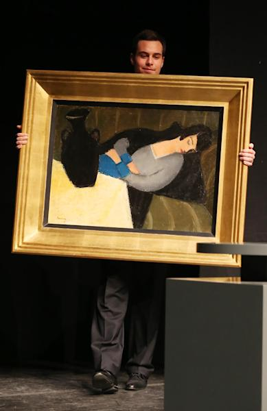 """A staff member of the gallery carries the painting """"Sleeping woman with black vase"""" by Hungarian artist Robert Bereny during an auction at the Judit Virag Gallery in Budapes on December 13, 2014 (AFP Photo/Ferenc Isza)"""