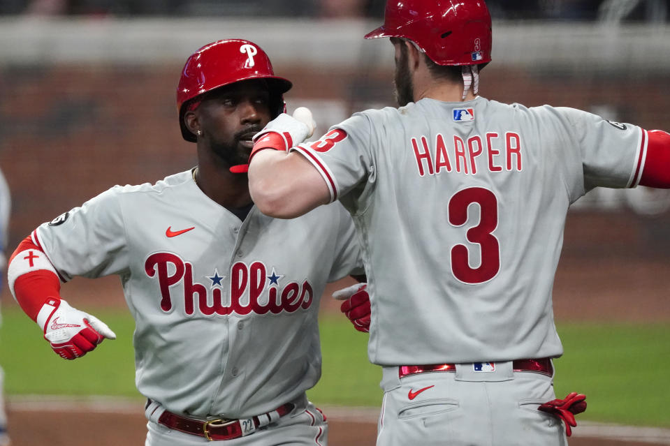 Philadelphia Phillies' Andrew McCutchen (22) celebrates with Bryce Harper (3) after hitting a solo home run in the fifth inning of a baseball game against the Atlanta Braves, Saturday, April 10, 2021, in Atlanta. (AP Photo/John Bazemore)
