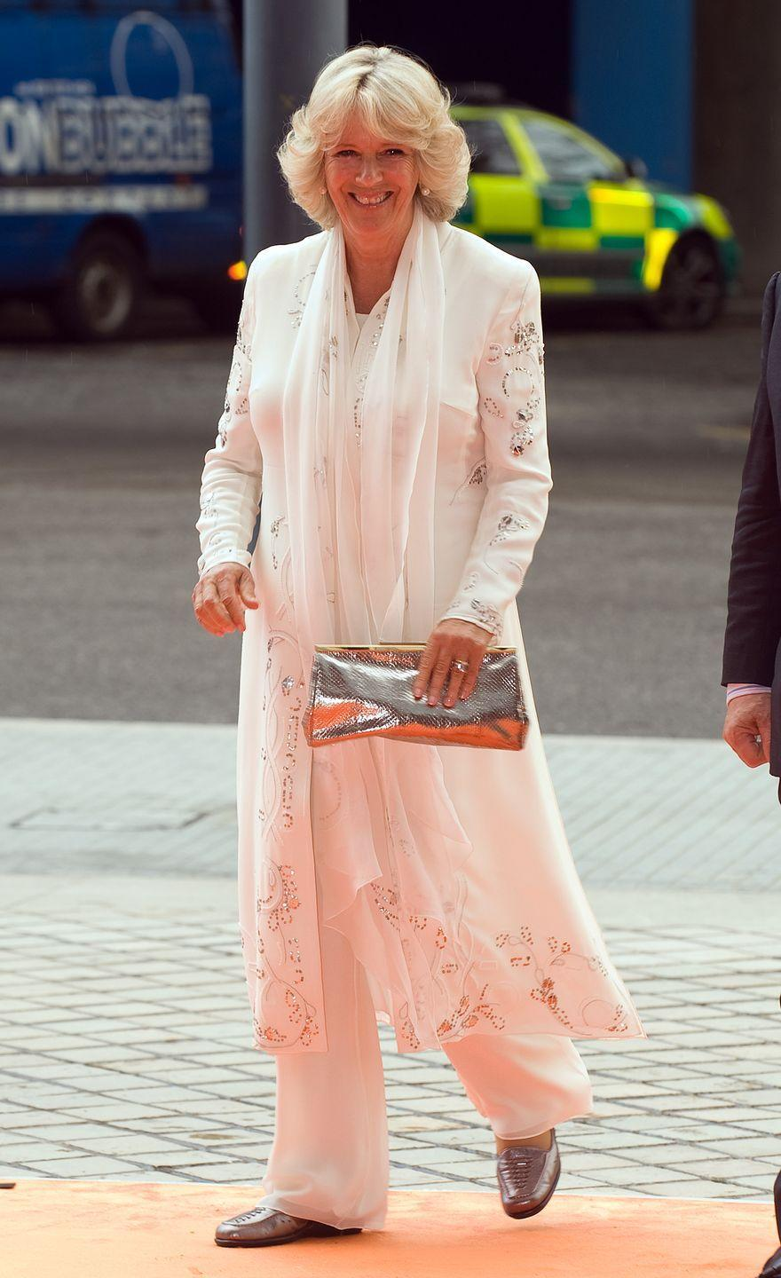 <p>On a day out in London, Camilla looked breezy in this flowing white coatdress with floral embroidery and matching white trousers. </p>