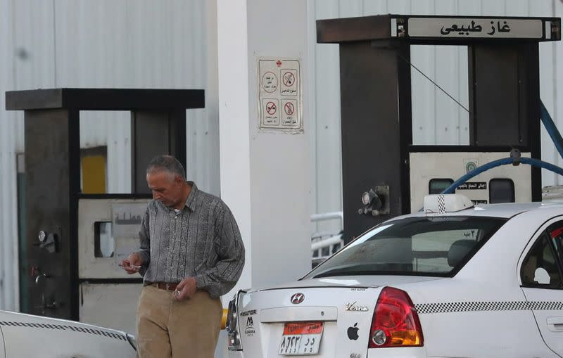 A taxi driver walks after he filled up with gas at Natural Gas Vehicles (NGV) petrol station in Cairo