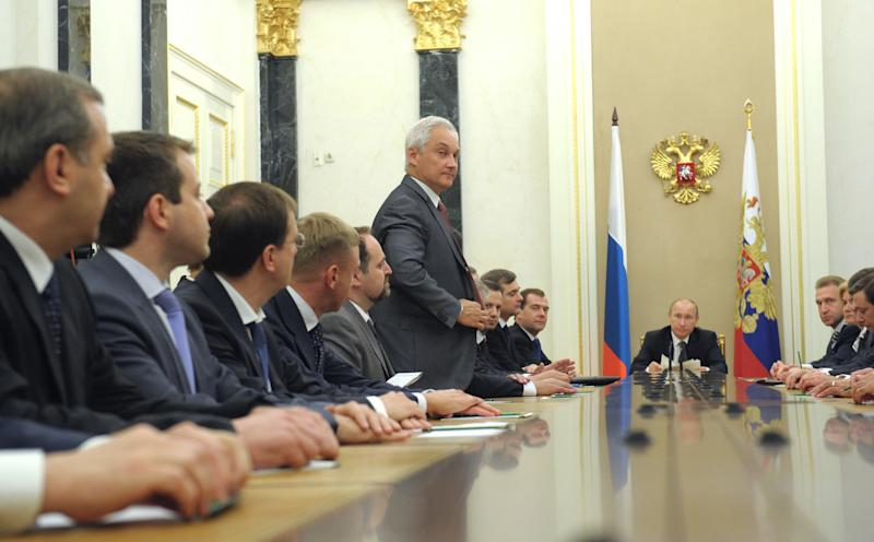 Russian President Vladimir Putin, center back, chairs a meeting with a new cabinet in the Kremlin in Moscow, Monday, May 21, 2012. Russian President Vladimir Putin named a new Cabinet Monday, warning its members that they will have to fulfill their duties in a difficult global economic climate. New Economics Minister Andrei Belousov, standing, is presented. (AP Photo/RIA-Novosti, Alexei Druzhinin, Government Press Service)