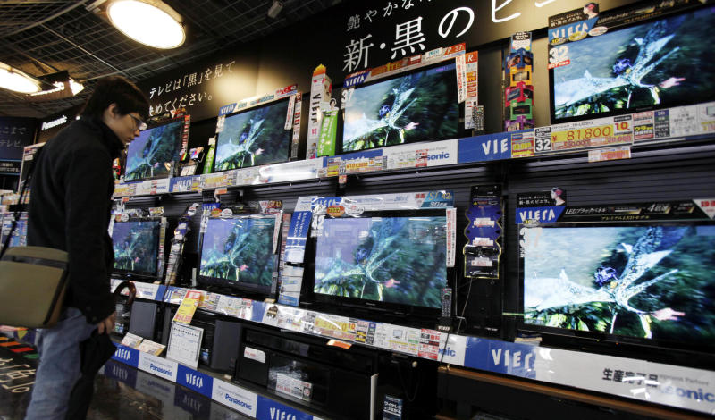 In this March 2, 2012 photo, a visitor inspects Panasonic's Viera TVs at a retail store in Tokyo. Consumer electronics giant Panasonic Corp. said Tuesday, July 31, it returned to the black in the April-June quarter, logging a net profit of 12.8 billion ($163 million) mainly on lower costs after cutting more than 38,000 jobs over the last year. (AP Photo/Koji Sasahara)